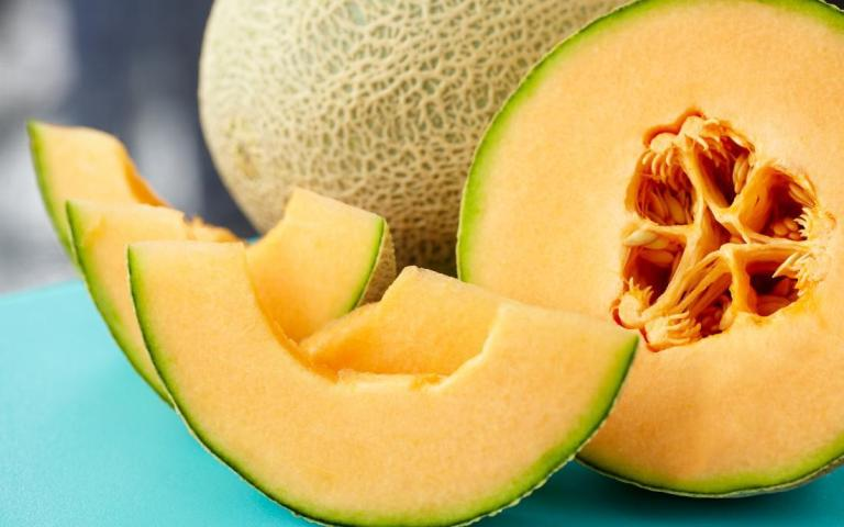 a-close-up-of-a-sliced-cantaloupe-on-a-blue-table